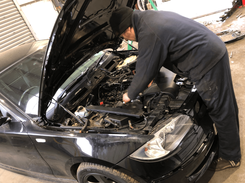A Mechanic completing engine work on a car at Michael Wicks Garage